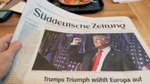 donald trump : FRANKFURT, GERMANY - NOV 10, 2016: POV of Man reading in German Café about the  Suddeutsche Zeitung newspapperwith Donald Trump elected as President as the 45th President of United States of America