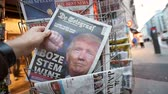 donald trump : PARIS, FRANCE - NOV 10, 2016: Man buying Dutch newspaper with De Telegraaf shocking headline title at press kiosk about the US President Elections - Donald Trump is the 45th President of United States of America Stock Footage