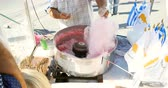 tatarak : PAPHOS, CYPRUS - CIRCA 2014: Senior man preparing cotton candy at the cotton candy machine operating rotation at fair carnival party during Ochi day with Greek and Cyprus flags and kids surrounding the machine
