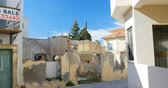 aluguel : PAPHOS, CYPRUS - CIRCA 2016: Pan over the sunny street of Phapos with ruins of a house and FOR SALE sign on another building and red telephone number - property in Greece Cyprus
