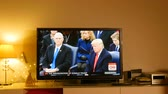 donald trump : PARIS, FRANCE - JAN 20, 2017 Man  listening watching TV news reporting 45th U.S. President Donald Trumps inauguration ceremony - Trump listens to Missouri State University Choral sings Now we belong: