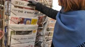 donald trump : PARIS, FRANCE - JAN 21, 2017: Woman purchases a Die Zeit German newspaper from a newsstand featuring photos and headlines with Donald Trump inauguration as the 45th President of the United States in Washington, D.C Stock Footage