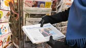 donald trump : PARIS, FRANCE - JAN 21, 2017: Woman purchases reading German newspaper Offenburger Tageblatt from a newsstand featuring headlines with Die Trump Show of Donald Trump inauguration as the 45th President of the United States in Washington, D.C