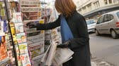 barack obama : PARIS, FRANCE - JAN 21, 2017: Woman purchases a Suddeutsche Zeitung German newspaper from a newsstand featuring headlines with Donald Trump inauguration as the 45th President of the United States in Washington, D.C