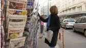donald trump : PARIS, FRANCE - JAN 21, 2017: Woman purchases a LAlsace French newspaper from a newsstand featuring headlines with Donald Trump inauguration as the 45th President of the United States in Washington, D.C Stock Footage