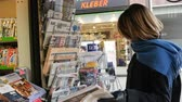 manchete : PARIS, FRANCE - JAN 21, 2017: Woman purchases a The Wall Street Journal US newspaper from a newsstand featuring headlines with Donald Trump inauguration as the 45th President of the United States in Washington, D.C Vídeos