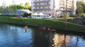 kürek çekme : STRASBOURG, FRANCE - CIRCA 2017: group of kids kayaking on Ill river in Strasbourg in front of Francesca restaurant and a few meter from European Parliament and ECHR