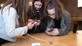 plusz : STRASBOURG, FRANCE - APR 27, 2016: Group of teenager friends girls testing playing on the latest iPhone smartphone in Apple Store.  Apple iPhone tends to become one of the most popular smart phones in the world in 2016 Stock mozgókép