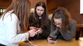 tornar : STRASBOURG, FRANCE - APR 27, 2016: Group of teenager friends girls testing playing on the latest iPhone smartphone in Apple Store.  Apple iPhone tends to become one of the most popular smart phones in the world in 2016 Stock Footage