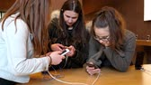 dual : STRASBOURG, FRANCE - APR 27, 2016: Group of teenager friends girls testing playing on the latest iPhone smartphone in Apple Store.  Apple iPhone tends to become one of the most popular smart phones in the world in 2016 Stock Footage