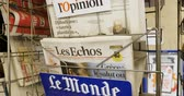 newspaper stack : PARIS, FRANCE - CIRCA 2017: Le Monde, Charlie Hebdo and other French press newspaper from a newsstand featuring headlines with international news