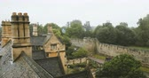característica : Pan over aerial view over rainy Oxford roofs from the windows of the New College - Oxford university footage.