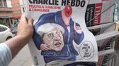 charlie hebdo : PARIS, FRANCE - JUN 12, 2017: Man point of view personal perspective buying at press kiosk satire newspaper Charlie Hebdo with Theresa May without head caricature with reactions to United Kingdom general election of 2017 - May fights to remain PM Stock Footage