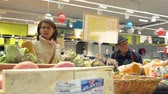 grocer : PARIS, FRANCE - CIRCA 2017: Supermarket scene with young French woman and senior man buying fruits and vegetables using the electronic weight Stock Footage