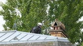 метла : London, United Kingdom - Circa 2017: Rear view of chimney sweeper working on the chimney on a roof top wearing security helmet and protection Стоковые видеозаписи