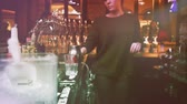 brewed : PARIS, FRANCE - CIRCA 2016: Vintage film - young beautiful female bartender brining beer preparing cocktails  for client at bar - tilt-shift lens to make beautiful silhouette and for moody atmosphere