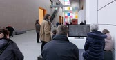 посещающий : STRASBOURG, FRANCE - CRICA 2017: Strasbourg Museum of Modern and Contemporary Art interior with people watching on large format plasma tv screen about the upcoming exhibition