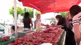 grande grupo de objetos : Strasbourg, France - circa 2017: Farmers selling to customers strawberries and tomatoes at the traditional French farmer market in Strasbourg - buying Alsace cherries organic bio food Stock Footage