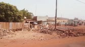 humanitarian : BAMAKO, MALI - CIRCA 2017: View from the humanitarian mission transportation vehicle of the poor street of the Bamako, people commuting near the destroyed buildings, selling goods etc.