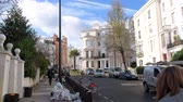 vitoriano : London, United Kingdom - Circa 2017: Expensive townhouses and other real estate in London on a warm spring day with cars and pedestrians commuting Stock Footage