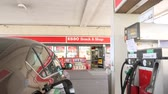 stacja paliw : BERLIN, GERMANY - CIRCA 2017: Pan from the fuel pump to the Esso gas station and the nearby car filling pump gas fuel petrol refueling. Esso is part of ExxonMobil