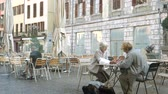 pincér : CHAMBERY, FRANCE - CIRCA 2017 Two senior women talking on the cafe outdoor terrace in central square early in the morning in front of Ernest cafe Place Saint-Leger time lapse fast motion
