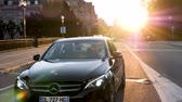 royalty free movie : STRASBOURG, FRANCE - CIRCA 2017: Avenue de la Liberte with impressive view of the Palais du Rhin at sunset and Luxury Mercedes-Benz car waiting for the green light, Sun flare sunlight Stock Footage