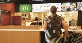 cukrzyca : FRANKFURT, GERMANY - CIRCA 2017: Interior of McDonalds fast food restaurant with female workers preparing the orders for the overweight mother with pram baby stroller