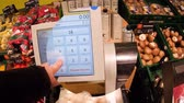 nagyobbítás : FRANKFURT, GERMANY - CIRCA 2017: Center loupe view of actions take by Male point of view at supermarket shopping for vegetables and fruits using electronic scale to weigh the mushrooms then put them in shopping cart