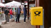 correspondência : Mummelsee, Germany - Circa 2017: Tourist having walking in slow motion slomo near open food terrace with main focus on the yellow postal box by Deutsche Post Stock Footage