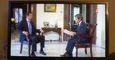 muhabir : PARIS, FRANCE - APR 20, 2015: Interview of Syrian President Bashar al-Assad to David Pujadas from France  TV asking about bombs and helicopters -  on TV screen in living room