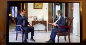 muhabir : PARIS, FRANCE - APR 20, 2015: Living room tv news Interview of Syrian President Bashar al-Assad to David Pujadas from France 2 TV asking about bombs and helicopters - Bashar explaining