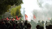 french communist party : STRASBOURG, FRANCE - SEPT 12, 2017: Crowd walking with smoke grenade protest demonstrators during a French Nationwide day of protest against labor reform proposed Emmanuel Macron