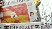 bajnok : PARIS, FRANCE - SEP 23, 2017: Man buying latest newspaper Die Zeit German press with portrait of Angela Merkel before the election in Germany for the Chancellor of Germany, the head of the federal government, currently Angela Merkel