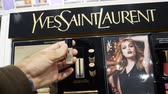 egész : PARIS, FRANCE - CRICA 2017: Male customer travestite buying Yves Saint Laurent female cosmetics in cosmetics fashion store on Champs Elysee