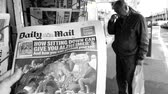lone gunman : PARIS, FRANCE - OCT 3, 2017: Man buying Daily Mail newspaper with socking title Pure Evil and photo at press kiosk about the 2017 Las Vegas Strip shooting in United States slow motion black and white