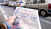 lone gunman : PARIS, FRANCE - OCT 3, 2017: Man reading De Telegraaf newspaper with socking title and photo at press kiosk about the 2017 Las Vegas Strip shooting in United States  slow motion Stock Footage