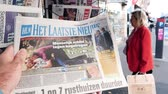 lone gunman : PARIS, FRANCE - OCT 3, 2017: Man reading het laatste nieuws newspaper with socking title and photo at press kiosk about the 2017 Las Vegas Strip shooting in United States 60 fatalities - slow motion Stock Footage