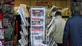 mandalay bay : PARIS, FRANCE - OCT 3, 2017: People Seniors buying international newspapers at Kiosk with socking title photos at about the 2017 Las Vegas Strip shooting in United States with about 60 fatalities and 527 injuries