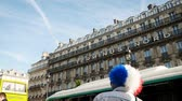 olympiáda : Paris, France - Circa 2017: Side view of sport fan male wearing wig with the French tricolor flag for a major sport event background Paris Architecture.  Paris is the capital to host the Olympic games 2024