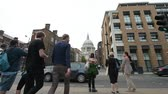 hristiyan : London, United Kingdom - Circa 2016: People waiting to cross the Queen Victoria Street to St Pauls Cathedral busy London street pedestrians, tourists visiting London commuting Stok Video