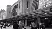 harry : LONDON, UNITED KINGDOM  - CIRCA 2017: large crowd of people commuting on the rush hour in London at the entrance of the Kings Cross train tube station near St Pancras International train station black and white Stock Footage
