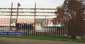 extremism : STRASBOURG, FRANCE - 14 Nov 2015: Tele-lens view of workers Council of Europe put all European Union Flags at half-mast in front of  Council of Europe following terrorist attack in Paris at Bataclan Stock Footage