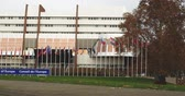 symbol of respect : STRASBOURG, FRANCE - 14 Nov 2015: Tele-lens view of workers of Council of Europe put all European Union Flags at half-mast in front Council of Europe following terrorist attack in Paris at Bataclan