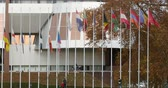 respeito : STRASBOURG, FRANCE - 14 Nov 2015: Tele-lens view of workers of Council of Europe put all European Union Flags at half-mast in front Council of Europe following terrorist attack in Paris at Bataclan