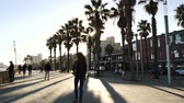 katalán : BARCELONA, SPAIN - CIRCA 2017: Pedestrians walking on a warm autumn fall day on the Passeig Maritim at Playa de la Barceloneta beach Stock mozgókép