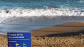 catalão : BARCELONA, SPAIN - CIRCA 2017: Platja de la Barceloneta or Playa de la Barceloneta beach signage and athletic professional male swimmer in the blue Mediterranean sea on a warm fall day - time lapse