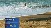catalão : BARCELONA, SPAIN - CIRCA 2017: Platja de la Barceloneta or Playa de la Barceloneta beach signage and athletic professional male swimmer in the blue Mediterranean sea on a warm fall day