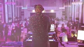 prima : Rear view of DJ mixing dancing in front his turntables and mixer and laptop during party wedding - illumination with laser light of his back and large room with guests flare