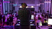 паз : Music DJ mixing dancing in front his turntables and mixer and laptop during party wedding - illumination with laser light of his back and large room with guests